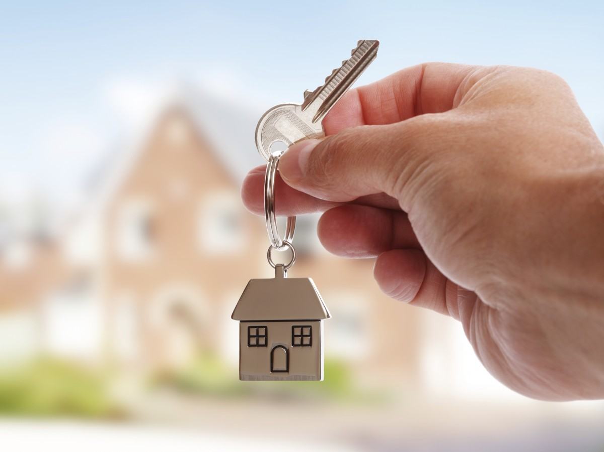 Holding house keys on house shaped keychain in front of a new home